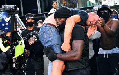 Black man carries injured white person to safety at London anti-racism protest