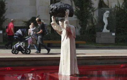 Sculpture of John Paul II throwing rock into red water makes waves