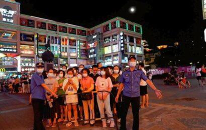 Chinese city locks down an area amid virus surge