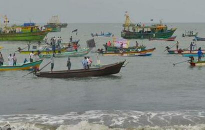 Fishermen ride boats with black flags in protest